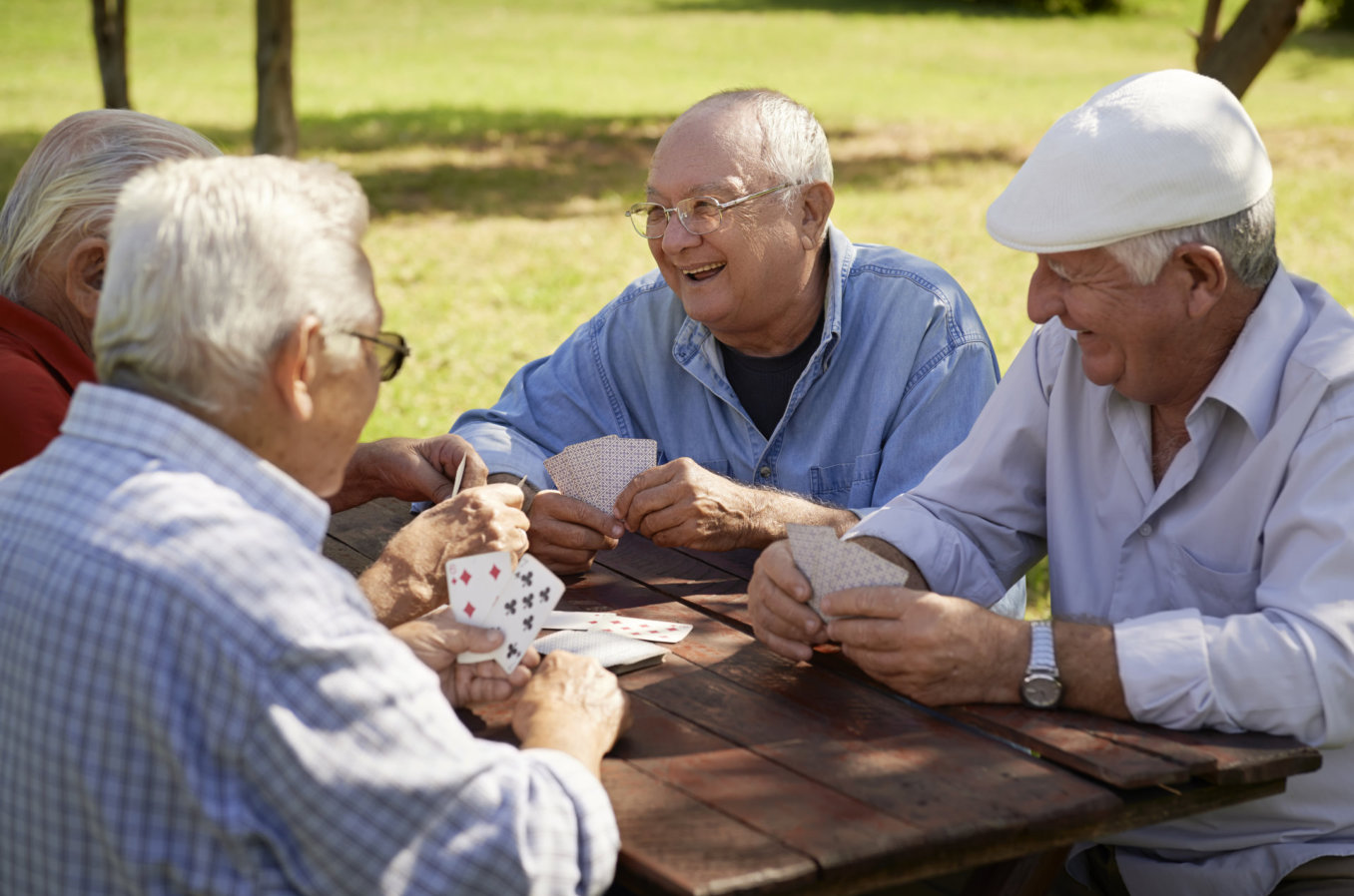 seniors smiling while playing cards