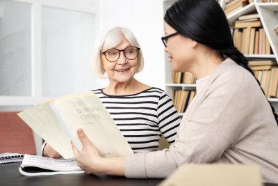 caregiver reading a book to the senior