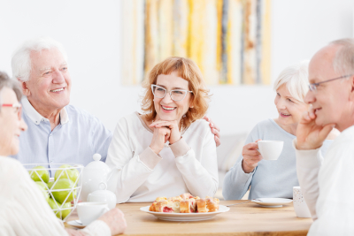 Happy elderly couple talking and laughing at tea party with friendly senior neighbors
